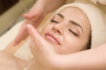 Young beautiful woman having facial massage