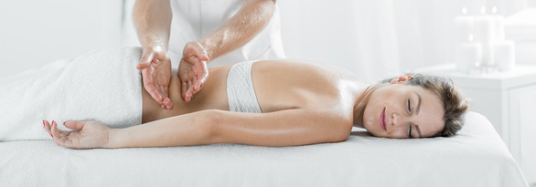 Panorama of content woman during therapeutic body massage